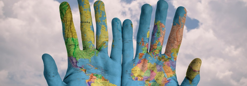 Hands holding a map of the world